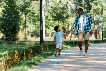 Photo for Happy african american kid holding hands with handsome father while walking in park - Royalty Free Image