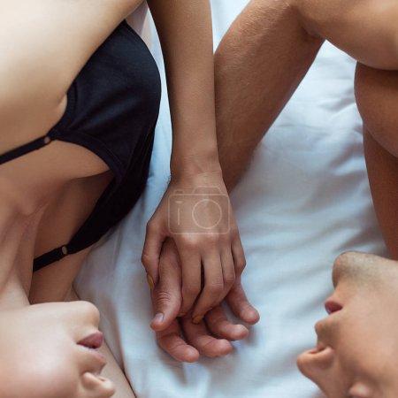 Photo pour Vue recadrée de l'homme et la jeune femme tenant la main tout en étant couché sur le lit - image libre de droit