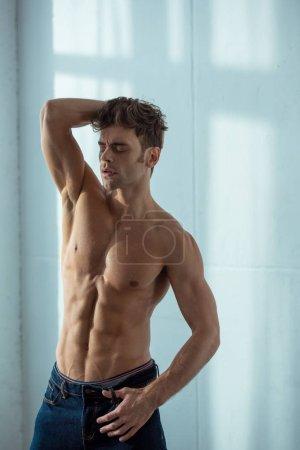 Photo for Sexy shirtless man in denim jeans standing in bedroom - Royalty Free Image