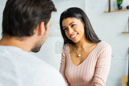 selective focus of smiling african american woman looking at man