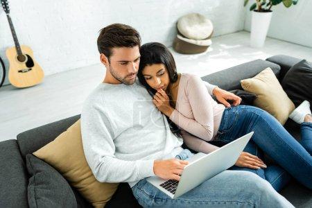 Photo pour Afro-américaine femme et bel homme regardant ordinateur portable - image libre de droit