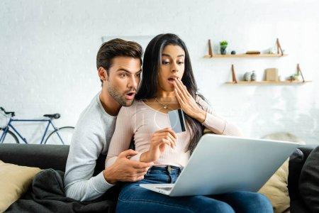 Photo pour Femme afro-américaine choquée tenant carte de crédit et regardant ordinateur portable avec l'homme - image libre de droit