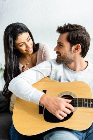 Photo pour Femme américaine africaine de sourire regardant l'homme avec la guitare acoustique - image libre de droit