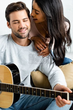 Photo for Smiling african american woman looking at man with acoustic guitar - Royalty Free Image