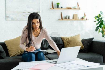 Photo pour Afro-américaine femme faire de la paperasse et en utilisant un ordinateur portable dans l'appartement - image libre de droit
