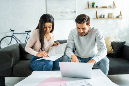 Photo for African american woman doing paperwork and handsome man using laptop in apartment - Royalty Free Image