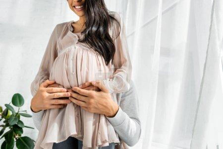 Photo pour Vue recadrée de l'homme étreignant le ventre de sa femme américaine africaine enceinte - image libre de droit