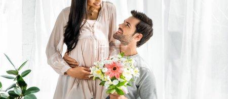 Photo pour Tir panoramique de be man hugging belly de sa femme américaine africaine enceinte et de fixation bouquet - image libre de droit