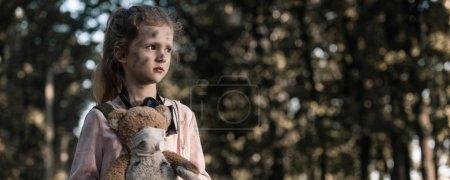 Photo pour Photo panoramique d'un enfant tenant un ours en peluche sale près d'arbres à Tchernobyl, concept post-apocalyptique - image libre de droit