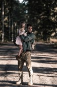 """Постер, картина, фотообои """"handsome and dirty man holding in arms kid in chernobyl, post apocalyptic concept"""""""