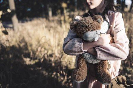 Foto de Vista cortada de los cabellos sucios sosteniendo oso teddy en chernoynes, el concepto post apocalíptico. - Imagen libre de derechos