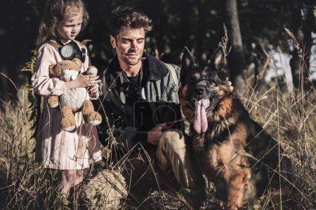 Photo pour Bel homme touchant berger allemand chien près de l'enfant avec ours en peluche, concept post apocalyptique - image libre de droit