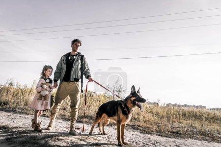 Photo pour Homme tenant la main avec mignon enfant près chien berger allemand sur la route, concept post apocalyptique - image libre de droit