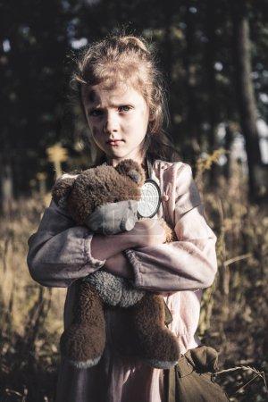 Photo pour Triste enfant tenant un ourson sale en peluche à chernobyl, concept post-apocalyptique - image libre de droit