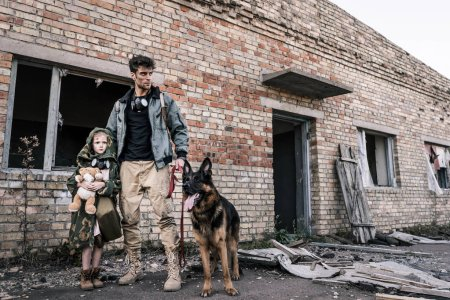 Photo for Handsome man standing with kid and german shepherd dog near abandoned building, post apocalyptic concept - Royalty Free Image