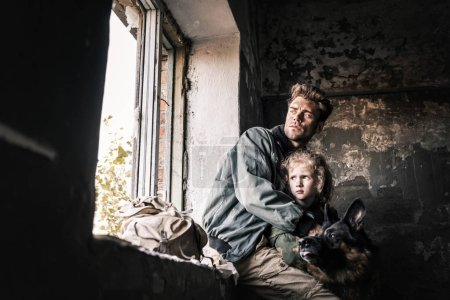 Photo for Man hugging dirty kid near german shepherd dog in abandoned building, post apocalyptic concept - Royalty Free Image