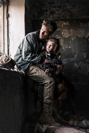 Photo pour Man hugging dirty child near german shepherd dog in abandoned building, post apocalyptic concept - image libre de droit