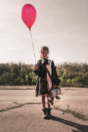 Photo for Cute kid with gas mask holding red balloon, post apocalyptic concept - Royalty Free Image