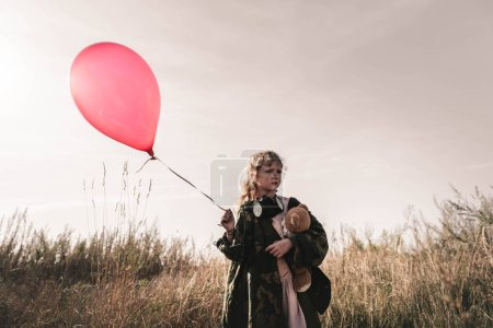 Photo for Selective focus of kid with gas mask and teddy bear holding balloon, post apocalyptic concept - Royalty Free Image