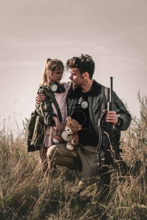 Photo for Handsome man holding gun near kid with teddy bear in field, post apocalyptic concept - Royalty Free Image