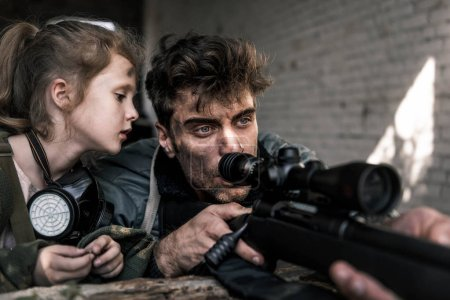 Photo for Selective focus of kid looking at man with gun, post apocalyptic concept - Royalty Free Image