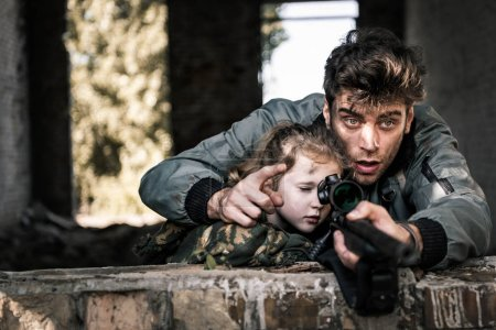 Photo for Selective focus of handsome man pointing with finger near kid and gun, post apocalyptic concept - Royalty Free Image