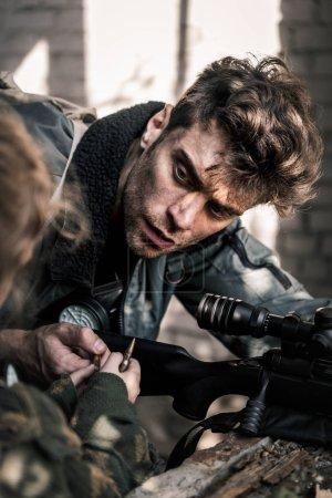 Photo pour Foyer sélectif de bel homme avec arme à feu prenant une balle près de l'enfant, concept post-apocalyptique - image libre de droit