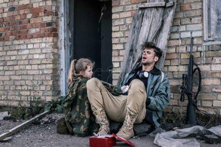 Photo for Kid holding medical bandage near man sitting on ground, post apocalyptic concept - Royalty Free Image