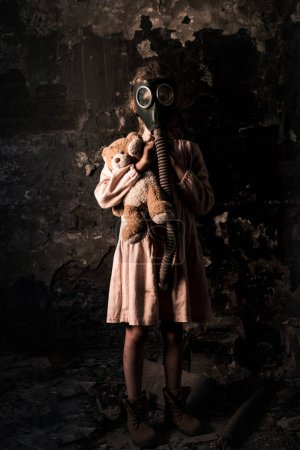 Photo for Kid in gas mask standing and holding teddy bear, post apocalyptic concept - Royalty Free Image