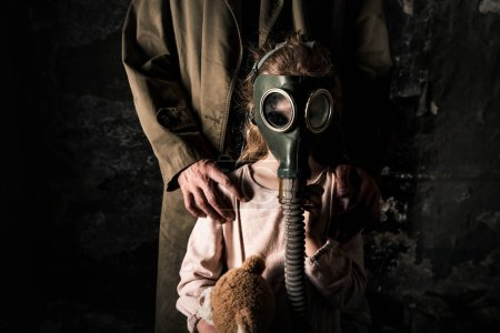 Photo for Cropped view of man standing near kid in gas mask, post apocalyptic concept - Royalty Free Image