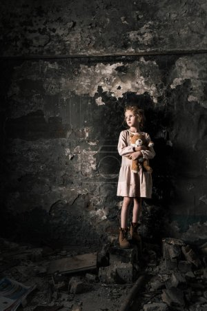 Photo pour Upset kid standing and holding teddy bear in dirty room, post apocalyptic concept - image libre de droit