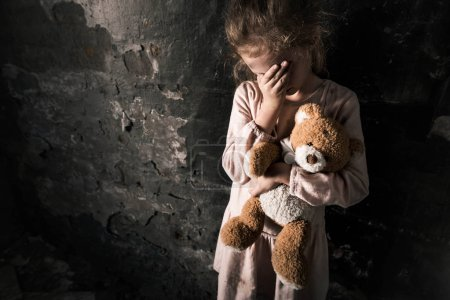 Photo for Upset kid touching face while holding teddy bear in dirty room, post apocalyptic concept - Royalty Free Image