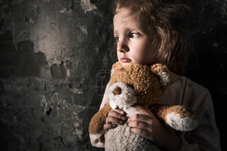 Photo pour Upset kid holding teddy bear in dirty room, post apocalyptic concept - image libre de droit