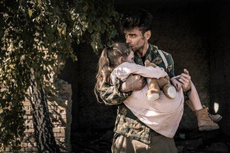 Photo pour Bel homme tenant dans les bras et embrassant enfant avec ours en peluche, concept post apocalyptique - image libre de droit