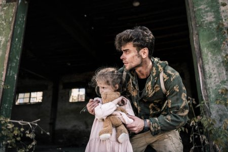 Photo for Handsome man standing with cute child outside, post apocalyptic concept - Royalty Free Image