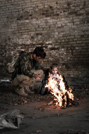 Photo for Selective focus of man wearing jacket on child while sitting near bonfire, post apocalyptic concept - Royalty Free Image