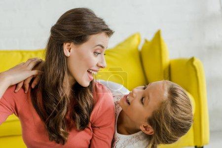 Photo pour Enfant heureux souriant tout en regardant baby-sitter joyeux dans le salon - image libre de droit