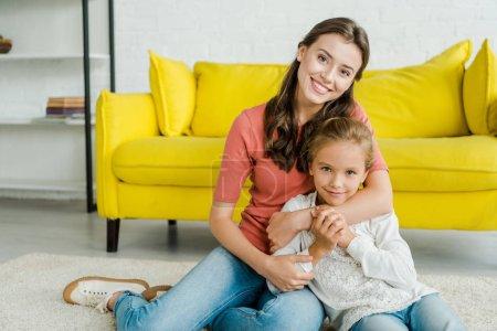 Photo pour Attrayant baby-sitter câlin heureux enfant dans le salon - image libre de droit