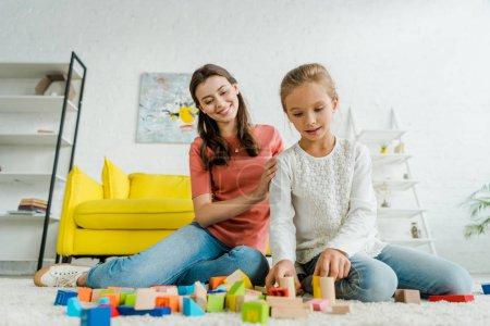 Photo pour Selective focus of kid playing with building bricks near babysitter - image libre de droit