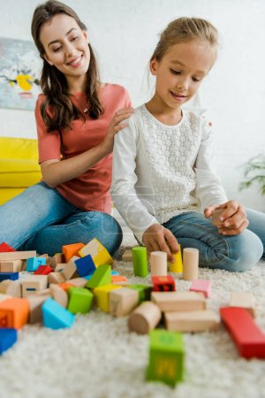 Foto de Selective focus of kid playing with toy blocks near cheerful babysitter - Imagen libre de derechos