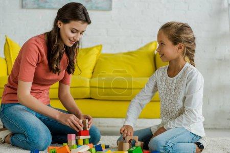 Photo pour Happy kid looking at babysitter near toy blocks on carpet - image libre de droit