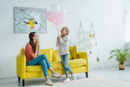 Photo for Cheerful babysitter sitting on sofa and looking at pink balloons near happy kid - Royalty Free Image