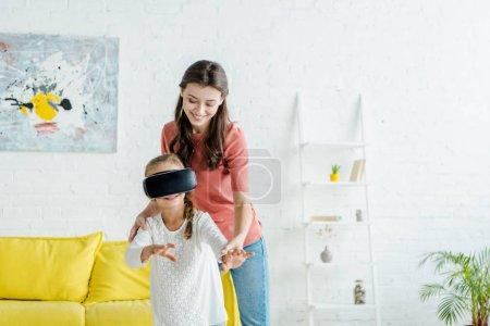 Photo pour Baby-sitter heureux debout avec mignon enfant en réalité virtuelle casque - image libre de droit