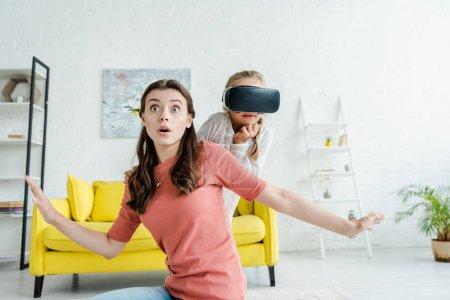 Photo pour Babysitter surpris avec les mains tendues près de l'enfant dans le casque de réalité virtuelle - image libre de droit