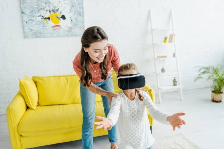 Photo pour Happy babysitter standing near cute child in virtual reality headset - image libre de droit