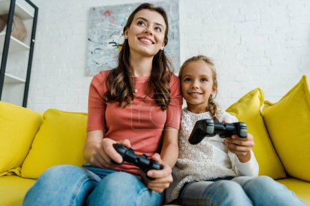 Photo for KYIV, UKRAINE - SEPTEMBER 4, 2019: babysitter and happy kid playing video game in living room - Royalty Free Image