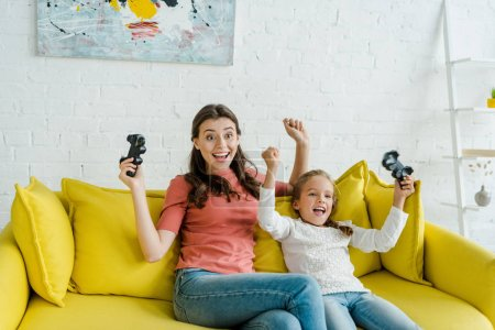 Photo pour KYIV, UKRAINE - SEPTEMBER 4, 2019: cheerful babysitter and excited kid celebrating triumph while holding joysticks in living room - image libre de droit