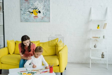 Photo pour Cheerful babysitter sitting on yellow sofa near kid drawing in living room - image libre de droit