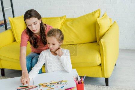 Photo pour Attrayant baby-sitter assis sur un canapé jaune près de l'enfant et crayons de couleur dans le salon - image libre de droit