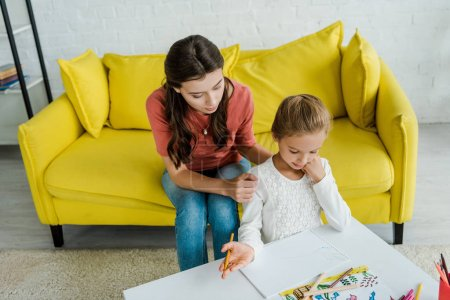 Photo pour Attractive babysitter sitting on yellow sofa near kid looking at drawn picture in living room - image libre de droit